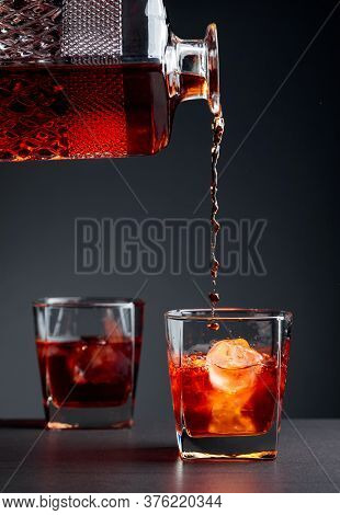 Whiskey Pours Into A Frosted Glass With Natural Ice. Alcoholic Drink Is Poured From A Crystal Decant