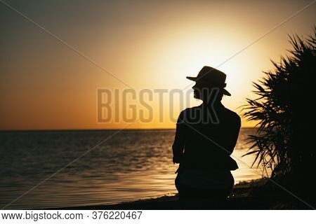 forces a girl who meditates at sunset on the sea