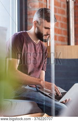 Selective Focus Of Concentrated Businessman Sitting On Window Bench And Using Modern Laptop