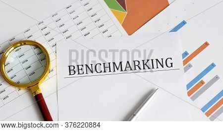 Text Benchmarking Is Written On A Paper With A Pen And A Magnifying Glass On The Table. Business Con