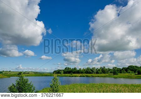Big White Clouds Float Over A Lake In A Forest Against A Blue Sky, Nature Traveling On Isolation. Na