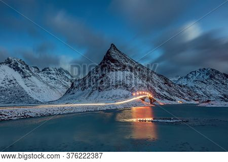 Road and bridge with traffic trails at night winter time. Fredvang bridge, Lofoten islands, Norway. Mountains and road. Landscape in the winter time. Bridge adove ocean. Norway travel