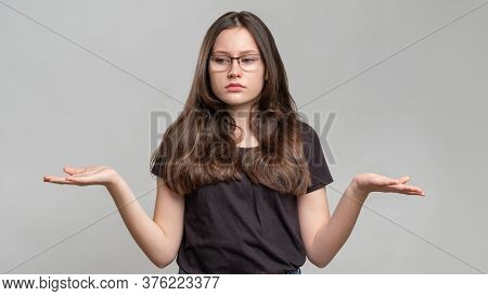 Clueless Woman Portrait. No Idea. Overwhelmed Lady Showing Shrug Gesture Comparing Options Isolated