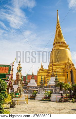 A Demon Guardian Statue With A Great Golden Stupa In Wat Phra Kaew Against The Sky, Temple Of The Em
