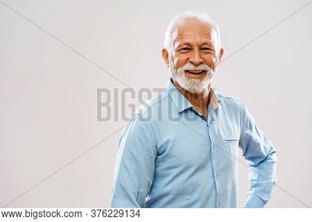 Studio Shot Portrait Of Cheerful Senior Man.