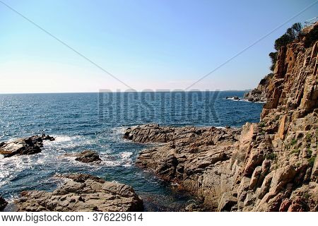 Rocky Coast Of The Mediterranean Sea. Beautiful View Of Rocks With Blue Sea With Waves, Horizon Unde