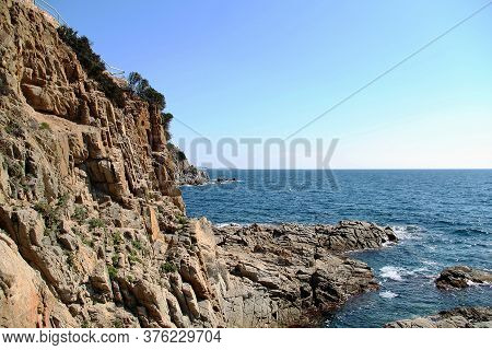 Rocky Coast Of The Sea. Spain Coast Of The Sea. Beautiful View Of Rocks With Green Pine Trees And Bl