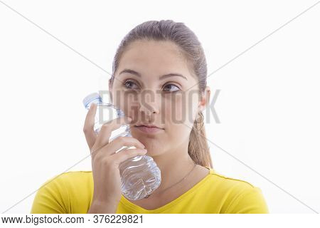 A Pensive Looking Beautiful Young Woman Holding A Bottle Of Water To Her Cheek. Healthy Lifestyle Co
