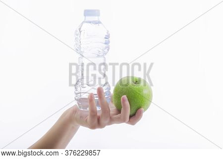Close Up Of A Young Female Hand Holding A Plastic Bottle Of Water And A Delicious Looking Green Appl
