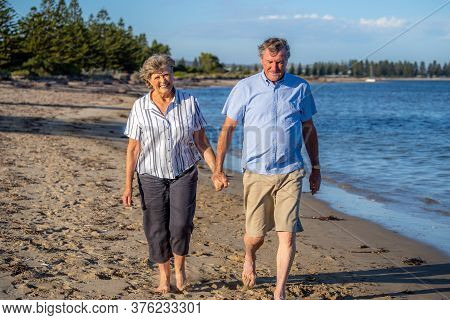 Healthy Active Senior Couple Holding Hands, Embracing Each Other And Walking On Beach