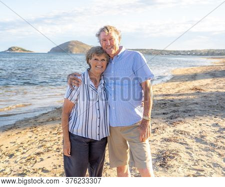 Portrait Of Happy Senior Couple At An Empty Remote Beautiful Beach On Sunny Day