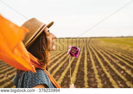 Beautiful Woman Walking In Nature. Happy People Lifestyle. Woman Holding Wildflower While Walking In