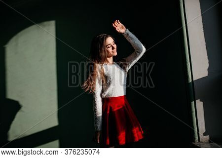 Romantic Brown-haired Lady Enjoying Sunlight While Posing In The Dark. Indoor Photo Of Graceful Whit