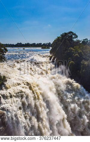 in Victoria National Park. The waterfall is located on the Zambezi River, on the border between Zambia and Zimbabwe. Concept of active, extreme and photo tourism