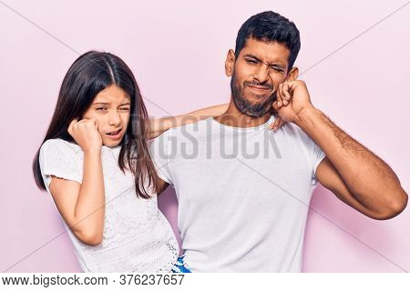 Young father and daughter wearing casual clothes covering ears with fingers with annoyed expression for the noise of loud music. deaf concept.