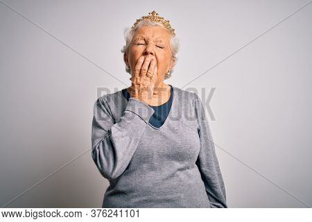 Senior beautiful grey-haired woman wearing golden queen crown over white background bored yawning tired covering mouth with hand. Restless and sleepiness.