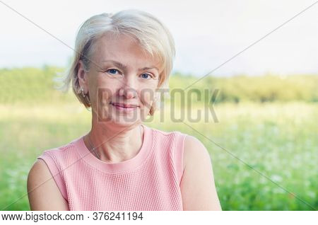 Portrait Of Positive Senior Adult Elegant Mature Middle Aged Blonde Woman Outdoors In Summer Backgro