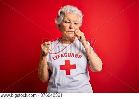 Senior beautiful grey-haired lifeguard woman wearing t-shirt with red cross using whistle mouth and lips shut as zip with fingers. Secret and silent, taboo talking