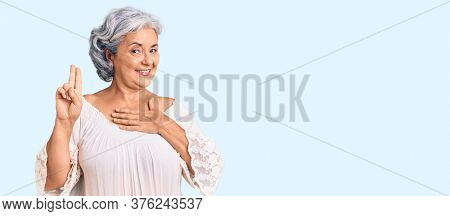Senior woman with gray hair wearing bohemian style smiling swearing with hand on chest and fingers up, making a loyalty promise oath