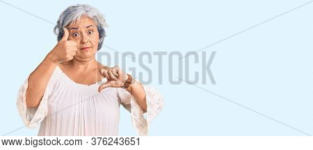 Senior woman with gray hair wearing bohemian style doing thumbs up and down, disagreement and agreement expression. crazy conflict