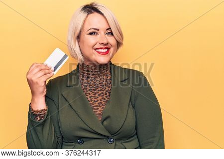 Young beautiful blonde plus size woman holding credit card over isolated yellow background looking positive and happy standing and smiling with a confident smile showing teeth