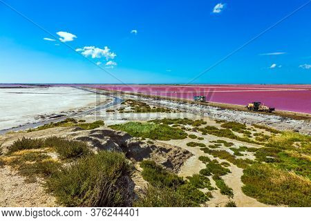 The Mediterranean coast of France, Camargue. Dark Pink Salt Water Bay. Salt production on the seashore. Huge truck rides along the bay with pink salt water. Concept of eco and photo tourism