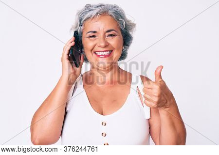 Senior hispanic grey- haired woman having conversation talking on the smartphone smiling happy and positive, thumb up doing excellent and approval sign