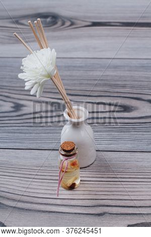 Aromatherapy Sticks And Decorative Spa Flower In A White Ceramic Vase. Spa Oil In Jar Near The Vase