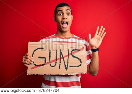 Young handsome african american man holding banner with prohibited guns message very happy and excited, winner expression celebrating victory screaming with big smile and raised hands