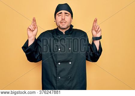Young handsome cooker man with blue eyes wearing uniform and hat over yellow background gesturing finger crossed smiling with hope and eyes closed. Luck and superstitious concept.