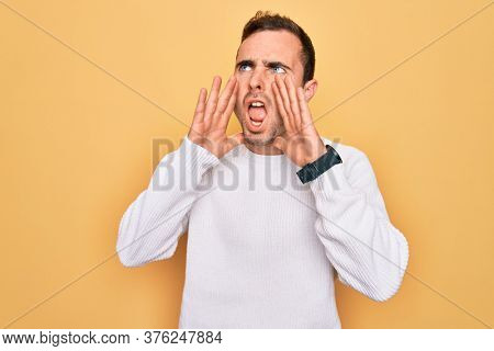 Young handsome man with blue eyes wearing casual sweater standing over yellow background Shouting angry out loud with hands over mouth