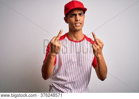 Young handsome african american sportsman wearing striped baseball t-shirt and cap Showing middle finger doing fuck you bad expression, provocation and rude attitude. Screaming excited