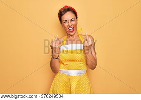 Middle age senior pin up woman wearing 50s style retro dress over yellow background Showing middle finger doing fuck you bad expression, provocation and rude attitude. Screaming excited
