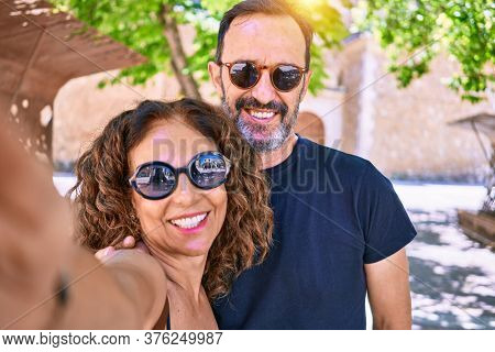 Middle age beautiful couple wearing casual clothes and sunglasses smiling happy. Standing with smile on face making selfie by the camera hugging at town street.