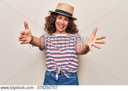 Middle age beautiful woman wearing striped t-shirt and hat over isolated white background looking at the camera smiling with open arms for hug. Cheerful expression embracing happiness.