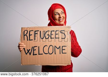 Woman wearing muslim hijab asking for immigration holding welcome refugees message serious face thinking about question, very confused idea
