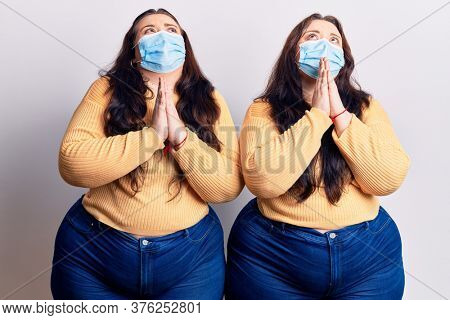 Young plus size twins wearing medical mask begging and praying with hands together with hope expression on face very emotional and worried. begging.