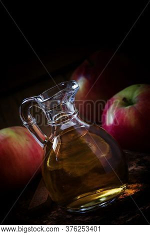 Apple Cider Vinegar In A Glass Jug, Fresh Apples, Dark Wooden Background In Rustic Style, Low Key, S