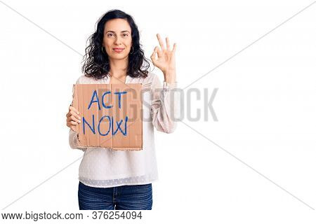 Young beautiful hispanic woman holding act now banner doing ok sign with fingers, smiling friendly gesturing excellent symbol