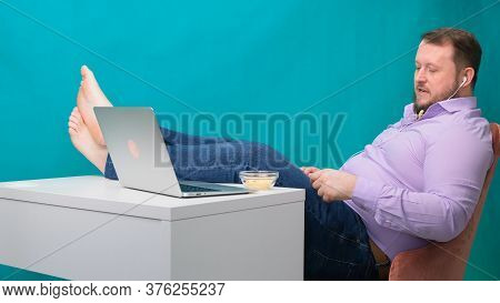 Close-up Businessman Being Lazy At The Workplace With Legs On The Table Eating Chips. The Concept Of