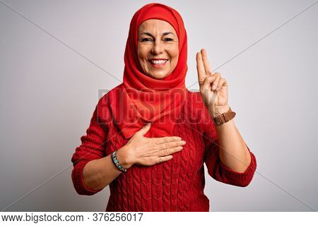 Middle age brunette woman wearing muslim traditional hijab over isolated white background smiling swearing with hand on chest and fingers up, making a loyalty promise oath