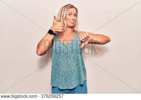 Middle age caucasian blonde woman wearing sportswear doing thumbs up and down, disagreement and agreement expression. crazy conflict