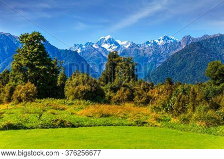 Great fields, forests and hills. The highest peak of New Zealand Mount Cook is covered in snows and glaciers. South Island of New Zealand. The concept of active and photo tourism