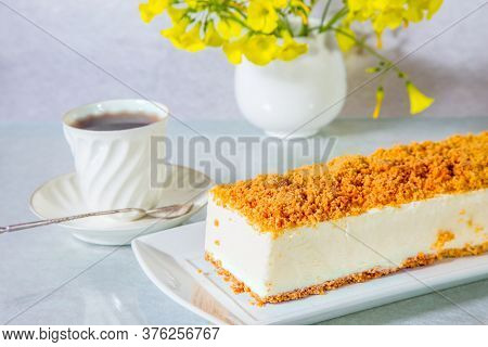 Gorgeous white cheesecake, sprinkled with sweet crumbs. Professional bakery. The background is  porcelain cup with hot tea and vase with daisies