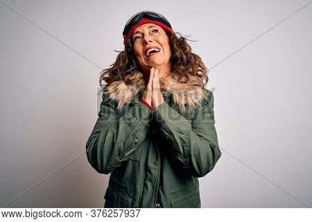 Middle age skier woman wearing snow sportswear and ski goggles over white background begging and praying with hands together with hope expression on face very emotional and worried. Begging.
