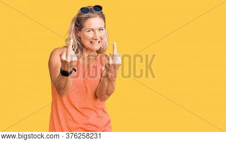 Middle age fit blonde woman wearing casual summer clothes and sunglasses showing middle finger doing  bad expression, provocation and rude attitude. screaming excited
