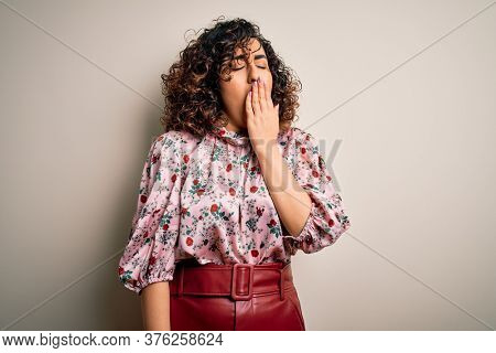 Young beautiful curly arab woman wearing floral t-shirt standing over isolated white background bored yawning tired covering mouth with hand. Restless and sleepiness.