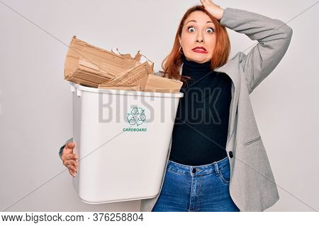 Young beautiful redhead woman recycling holding trash can with cardboard to recycle stressed with hand on head, shocked with shame and surprise face, angry and frustrated. Fear and upset for mistake.