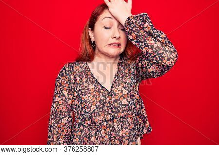 Young beautiful redhead woman wearing floral casual dress standing over red background surprised with hand on head for mistake, remember error. Forgot, bad memory concept.