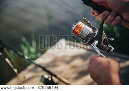 Young Fisherman Fishing On Lake Or River. Cut View And Close Up Of Mans Hands Holding Rod And Reel U